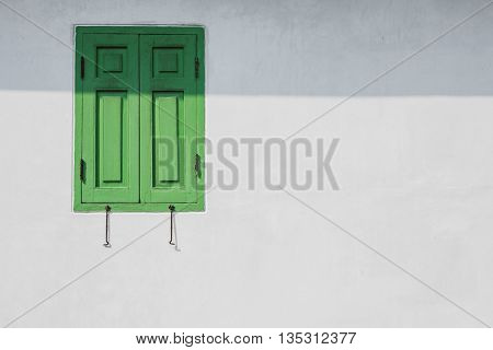 Green window on a white wall with shade from eaves. You can fill idea or text into space.