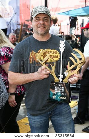 ARLINGTON, TX - APR 18: Rhett Akins holds the Top Archer trophy at the ACM & Cabela's Great Outdoor Archery Event at Globe Life Park in Arlington on April 18, 2015 in Arlington, Texas.