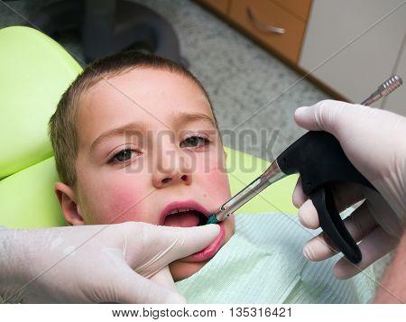 Preschool boy on dental prevention examination geting anesthesia