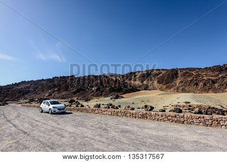 TEIDE, TENERIFE, SPAIN - DECEMBER 2015: Car parking among volcanic hills at Teide National par on Tenerife island, Spain