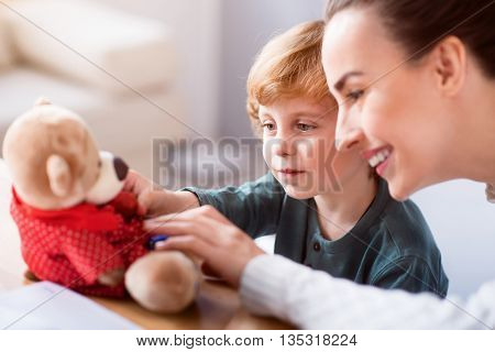 So soft. Amazing little boy and his mother sitting at the table and looking at the teddy bear and touching it