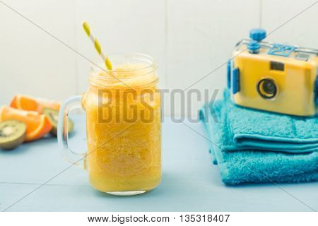 Juicy smoothie from orange mango or pineapple beachfront set with blue towels and camera healthy life concept summer vacation
