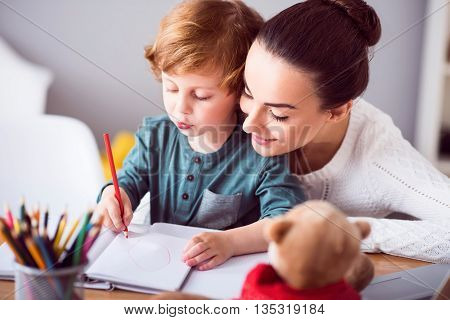 First lesson. Young contended mother sitting at the table with her little son and looking how he drawing