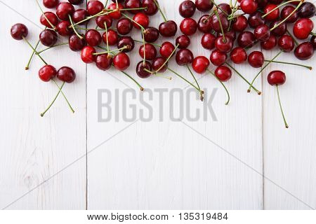 Sweet fresh cherries background. Scattered cherries on white rustic wood pattern with copy space. Cherry fruit backround. Garden fresh organic cherries at wooden table, top view. Food background.
