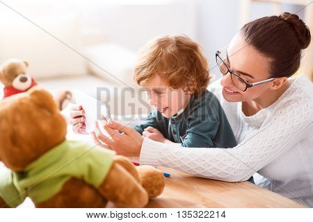 Move it. Contended mother playing on the tablet with her joyful little son while sitting with him at the table