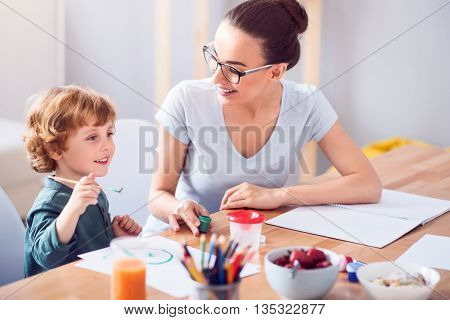 I like painting. Fascinated little boy holding a brush and looking in front of him while his mother holding a jar of painting and looking at him