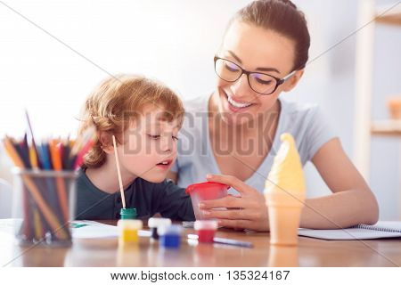 Look at that color. Little cute boy and his delighted smiling mother looking at the glass of water with interest while painting at the table