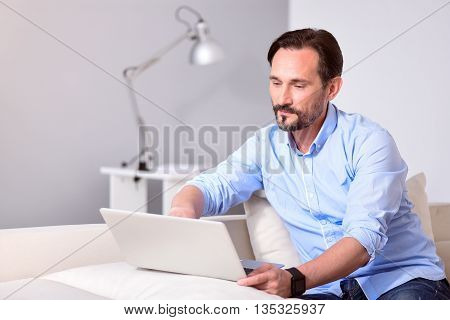 Relaxed work. Wistful mature bearded man sitting in front of the laptop on the couch