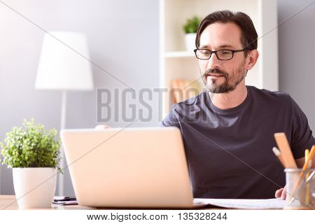 Hour for work. Serious mature bearded man with glasses and light smile looking at the screen of his computer