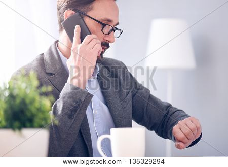 Fixing a meeting. Respectful bearded man with glasses looking at his smart watch while talking on the phone