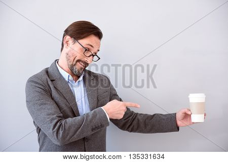 Strongly advise you. Pleasant respectable middle aged man pointing with his finger at a cup of coffee while standing isolated on the grey background