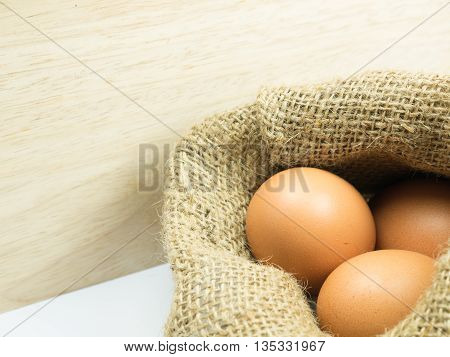three egg in sack on wooden and white background