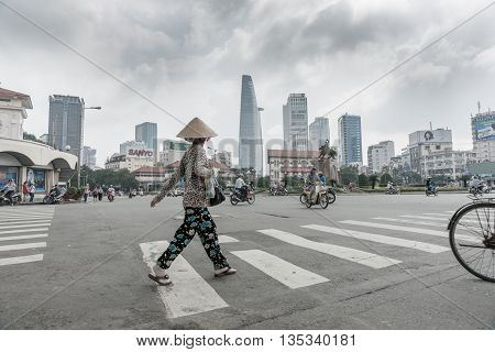 Saigon Ho Chi Min City, Vietnam - October 12, 2013; overcast sky desaturated colors at major intersection in the city with woman crossing on pedestrian crossing wearing coolee hat while motor bikes and cycles seem to randomly move about