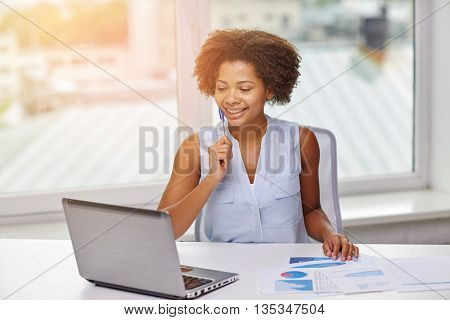 education, business, statistics and technology concept - happy african american businesswoman or student with laptop computer and papers at office