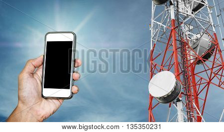 Mobile phone on hand with copy space, and telecommunication tower with satellite dish telecom network on blue sky with sun