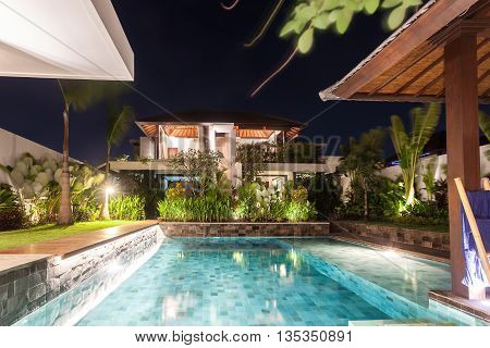 Modern House Including A Pool In The Middle At Night