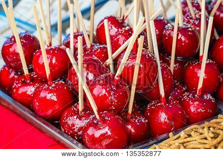 Sweet glazed red toffee candy apples on sticks for sale on farmer market or country fair.