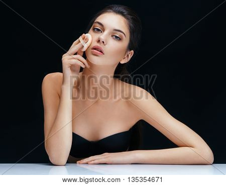 Young woman applying powder on her face with powder puff. Skin care concept