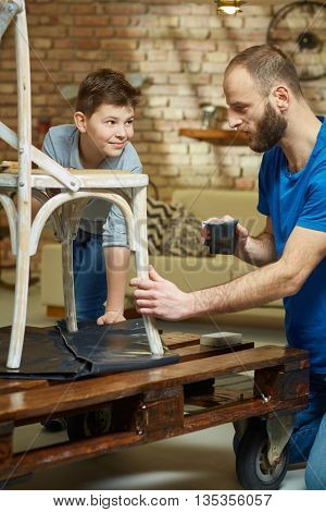 father and son tinkering at home, renewing chair.
