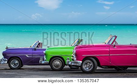 Most beautiful american classic cars parked before the beach in Cuba