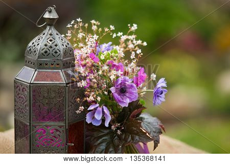 Garden style summer bouquet. Mix of lilac and purple anemone flowers, geranium flowers and heuchera or alumroot leaves. Bouquet with indian stile lantern. Garden style wedding bouquet. Flower design.