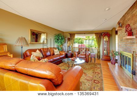 Cozy Grey Living Room Interior With Comfortable Leather Sofas. View Of Fireplace Built-in The Brick