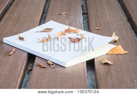 Low key photo of old white book on wooden table with dried leaves with dark tone and selection focus