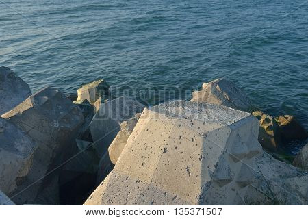 Close Up Of Breakwater Made Of Concrete Tetrapods In The Sunset, With The Calm Sea In Background. Se