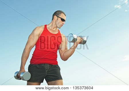 a young man trains with dumbbells outdoors in the red shirt and black shorts