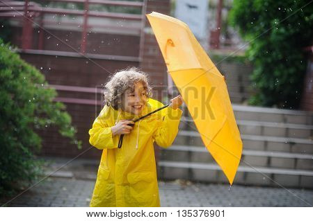 The amusing little boy in a yellow raincoat and with a yellow umbrella stand in the rain. Large drops of a rain fall to it on the head and he tries to open an umbrella.