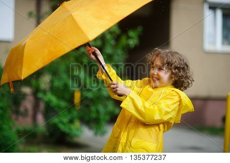 The boy 8-9 years in a bright yellow raincoat tries to hold an umbrella from wind flaws. He holds an umbrella with two hands. Child is in the yard of the house. He has a good mood