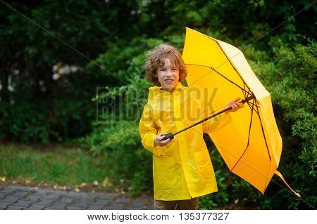 The boy in a raincoat with an umbrella in hands. The cute little fellow dressed in a yellow raincoat holds a yellow umbrella. He looks in the camera. Behind his back magnificent green vegetation.