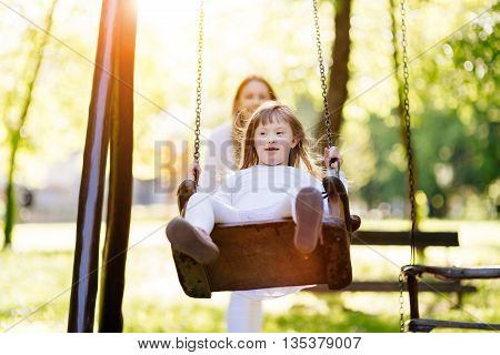 Disabled child enjoying the swing outdoors with sister