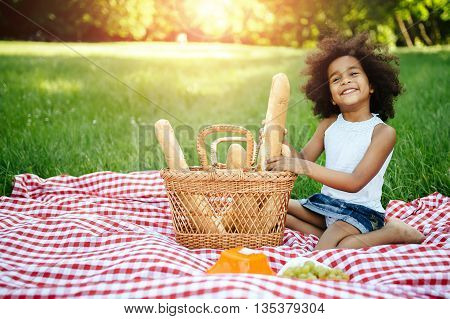 Beautiful afro kid holding baguette while picnicking