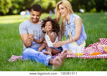 Beautiful cheerful faimly outdoors enjoying picnic outing