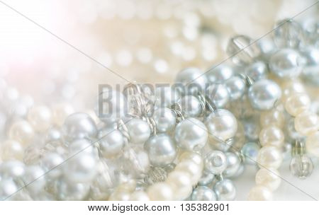Blurred pearl necklace with blurred background on white. Macro shot Shallow depth of field defocused