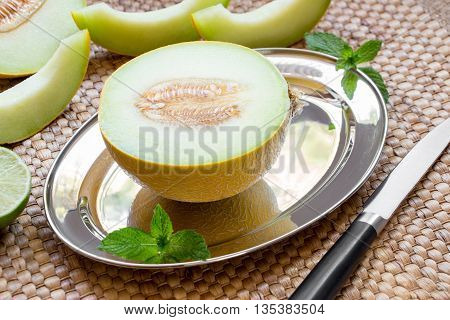 Diagonally at the center on a silver platter half of melon near melon slices, mint leaves, knife on a straw napkin background. Half of melon on silver platter. Horizontal. Close.