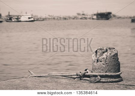 A mooring on a dock in a port keeps an old fishing trawler tethered in place.