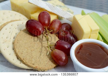 Cheese and Crackers with grapes, celery and chutney