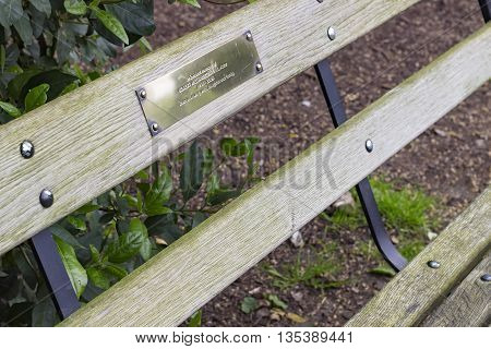 London England - May 22 2016: In Battersea Park close up of a bench built in memory of the actor Robert William Tunstall who passed in 2005.