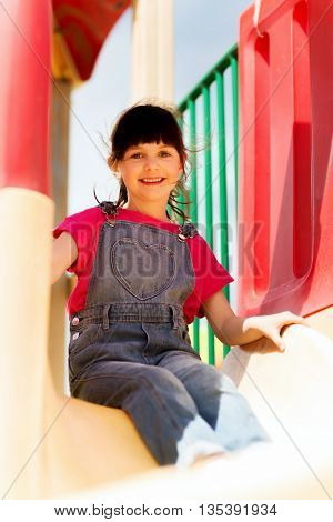 summer, childhood, leisure and people concept - happy little girl sliding on slide at children playground