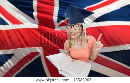 people, national education, knowledge and graduation concept - smiling young student woman in mortarboard and eyeglasses with encyclopedia book pointing finger up over english flag
