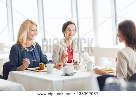 people, food, communication and lifestyle concept - happy women eating dessert and talking at restaurant