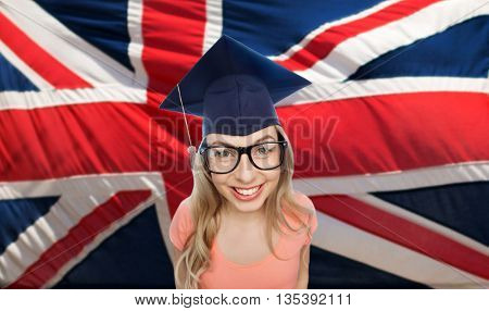 people, graduation and national education concept - smiling young student woman in mortarboard and eyeglasses over english flag