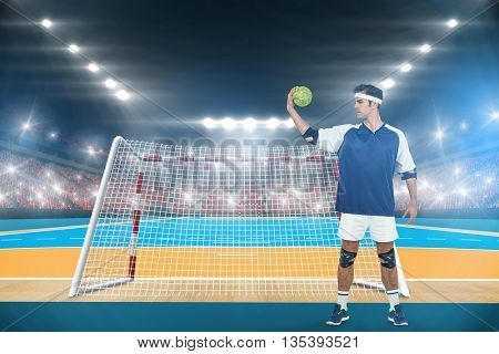 Sportsman posing with ball on white background against handball field indoor