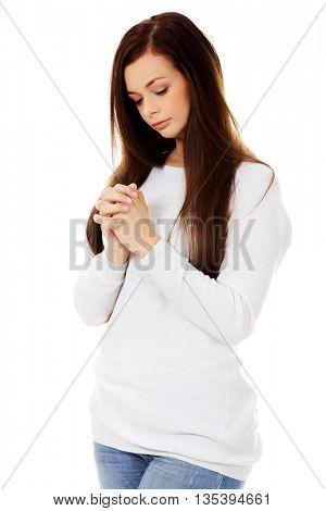 Beautiful young caucasian woman praying