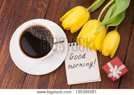 Cup of coffee, tulips and Good morning massage on wooden background