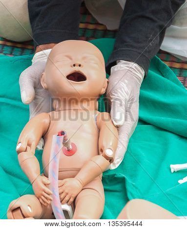 Doctor, paramedic,  The refresher training to assist childbirth newborn with medical baby dummy in emergency the midwife.(select focus baby dummy) poster