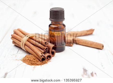 Ground Cinnamon, Essential Oil And Cinnamon Sticks Cinnamon On A White Background