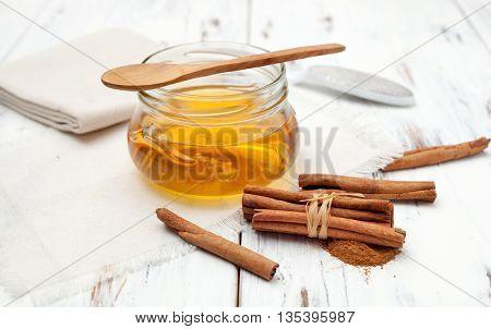 Ground Cinnamon, Honey And Cinnamon Sticks On White Background